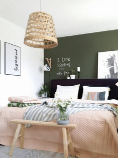 You can't go wrong with a deep green accent wall paired with peachy pinks.