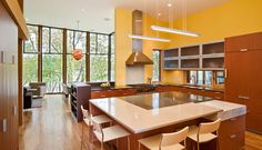 Inside this modern house, a yellow kitchen with wood cabinets and a large kitchen island has lots of surface area for prepping food.