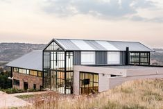 Architect Nadine Engelbrecht has designed a stunning, off-grid home in South Africa complete with a massive conservatory. Take a tour of this beautiful house. Conservatory House, Greenhouse House, Off Grid, Brick Siding, Small Barns, Glass Facades, Architect House, Metal Roof, Industrial Style