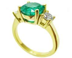 Three stone emerald engagement ring yellow gold