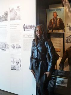 A photo of Deidra McGee standing in front of the Triple Nickles' photo Exhibit at the Smithsonian's National Museum of African American History and Culture