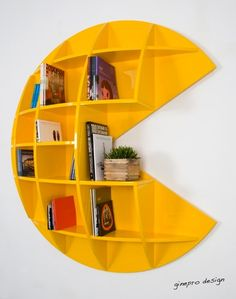 Puckman bookcase is made of shining varnished wood. The yellow color reminds us of the famous character of the 80s cult video game Pacman.