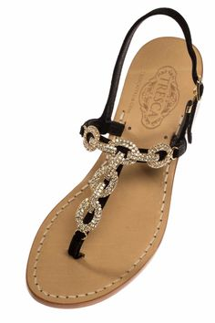 """Zia is cute and chic with her gold stoned chain loops and black Italian leather suede straps. Our soles are European sizes made in Italy. They are made from Italian leather with a wrapped, wooden heel. If you're a half size, size up. All of our Italian sandals are handmade to order by our cobbler in store. We offer a 1/2"""" flat as well as a 1"""" heel. Because each is unique and made-to-order, please allow up to 5 business days to ship. All custom shoes are final sale.   Zia Italian Sandal by…"""