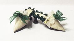 Cream shoes made in pure silk with black hand sculpted soles and black waisted heels. the fronts are decorated with a dark green bow and jewel embellishment the sides are decorated with matching braid. The top front of the shoes have lace and 2 tiny jewels to each side. Shoes come with lined box and carrier bag.  Approximately 2.2 cm long from heel to toe. Hand crafted by Michelle.