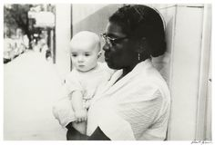 Standing on the sidewalk, a black woman holds a white child in Robert Frank's photograph. Description from theamericansattheackland.web.unc.edu. I searched for this on bing.com/images