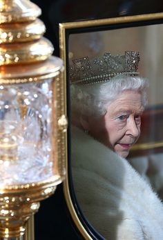 Britain's Queen Elizabeth II looks out from her carriage as she leaves after the State Opening of Parliament at the Houses of Parliament on May 27, 2015 in London, England.