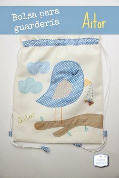 Bolsa para guardería personalizada en tonos azules con un pajarito y el nombre bordado a mano. Con interior semi-impermeable y bolsillo interior.
