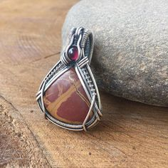 This beautiful wire wrapped pendant contains a noreena jasper cabochon topped with a small garnet cabochon nestled in sterling and fine silver wires. The jasper is quite beautiful and earthy looking, reminding me of the colors of autumn. This pendant measures 1 3/4 inches in length