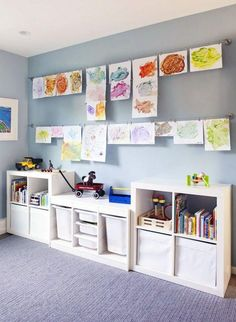 toys aligned against one long wall in bins.  paintings hung above.