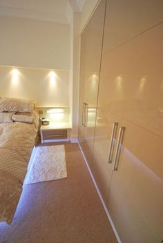 Cream high gloss fitted bedroom furniture with lighting.