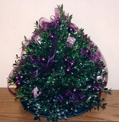 Purple Boxwood Tree. Sheer lavender ribbon, silver gift packages and deep purple glass balls.