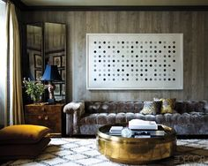 i like things in this room. loooong velvet couch. round, gold coffee table. wall texture. mirrored room divider.