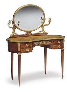 A FRENCH ORMOLU-MOUNTED MAHOGANY, KINGWOOD AND TULIPWOOD LADY'S DRESSING-TABLE<br />EARLY 20TH CENTURY <br />The ovoid dressing mirror flanked by two pairs of acanthus-sheathed candlearms, over a kidney-shaped top and conforming case set with four drawers, on tapering legs with foliate-cast sabots, the reverse of the mirror inscribed <i>AG 71</i> and <i>AG 72</i><br />52 in. (132 cm.) high; 44½ in. (113 cm.) wide; 20 7/8 in. (53 cm.) deep <br />