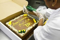Rosa Malpica, head cake decorator at Wright's Gourmet House in Tampa, puts the finishing touches on an anniversary cake. Cursive is he...