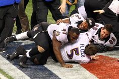 NEW ORLEANS, LA - FEBRUARY 03:  Joe Flacco #5 of the Baltimore Ravens is tackled while celebrating with teammates  Arthur Jones #97, Tyrod Taylor #2, and Dennis Pitta #88 following their 34-31 win against the San Francisco 49ers during Super Bowl XLVII at the Mercedes-Benz Superdome on February 3, 2013 in New Orleans, Louisiana.  (Photo by Dilip Vishwanat/Getty Images)