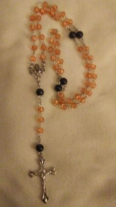 The Orange Marmalade Rosary. Orange Hail Mary beads, slightly bigger black marbled Our Father beads.. Centerpiece is a fleur-de-lis, depicting scenes from Lourdes. Great gift! https://www.etsy.com/listing/489666915/orange-marmalade-rosary?ref=shop_home_active_1