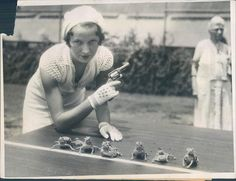 1930s girl in a very cute looking knit set, getting ready to fire the starting pistol for a horned toad derby. Bizarre!
