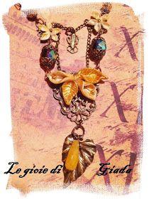 Collana composta da apette in bronzo, perle rosa fluo di swaroskvi, perle di vetro, fiori su filigrana creati in pasta you clay, come centr...