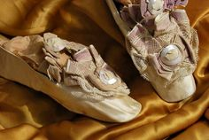 1830-1840: Ladies fancy silk slippers dating to the second quarter 19thc. With French Rue de Paix paper label, retailed out of a Boston shop, a bit rare to find.   Ruffled trimmings in silk and lace with ruffled strap and MOP buckles.  Silk casing over kid, straights