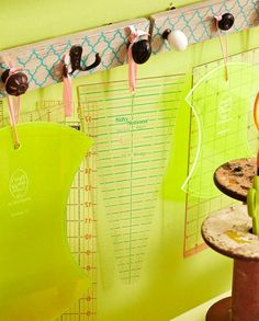 Stacking rules on uneven surfaces can warp them. Why not hang them instead? Turn old doorknobs and metal hooks into hangers by mounting them on a pretty painted 2x4 that then can be hung on a wall. Tie ribbons through the holes in the rulers and hang them from the knobs and hooks.