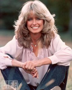 "Farrah Fawcett Becomes a Major Star  In 1975, Fawcett displays the feathered blond mane and gleaming smile that, within a year, will make her a star on TV's ""Charlie's Angels"" and the most iconic pinup of the 1970s."