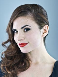 Hayley Atwell looking fantastically retro with red lipstick and side parted wavy hair.
