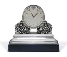 A SILVER MANTEL CLOCK DESIGNED BY JOHAN ROHDE  MARK OF GEORG JENSEN AND WENDEL, COPENHAGEN, 1945-1951  On a black stone rectangular base, the clock circular and set on scrolling foliage and berries and a stepped base. Christie's.
