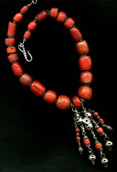 Maria Estrella Iglesias     Large red Dutch trade beads, stranded with a very old sterling silver Middle Eastern pendant containing natural old Mediterranean coral.