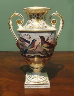 "1800 A Bloor Derby Two-Handle White Ground & Gilt Urn With a central panel depicting exotic birds in a landscape. Bearing ""Bloor Derby"" manufacturer's label."