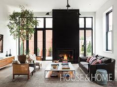 A monolithic, black Cambrian stone fireplace with a supersize firebox lends visual weight to the living area in this Toronto home. | Photographer: Donna Griffith | Designer: Mazen El-Abdallah