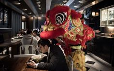 A performer providing a lion dance for a restaurant as part of celebrations of the Chinese lunar new year plays around with a customer having his lunch in Hong Kong