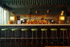 At the McCarren Hotel and Pool in Williamsburg, Brooklyn, papier-mâché animals from John Derian are mounted above the lobby bar. The striped awning fabric is by Perennials.