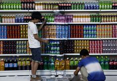 "Real life ""where's Waldo"" Liu Bolin is painted to blend into rows of drinks in his artwork entitled 'Plasticiser,' to protest against the use of food additives"
