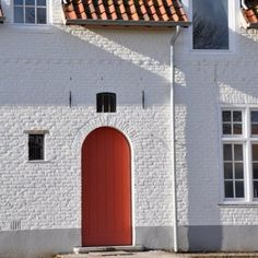 The red front door with tiny window.