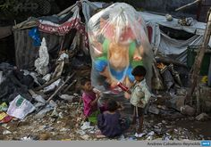 Indian children play in front of a Ganesh statue, wrapped in plastic for protection, being sold near the road ahead of the Ganesh Chaturthi festival in New Delhi on September 2, 2013. The Hindu festival which celebrates the rebirth of the God Lord Ganesha, starts September 9 and culminates on September 19, with many of the statues being immersed in bodies of water. AFP PHOTO/Andrew Caballero-Reynolds