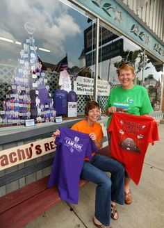 Debbie Sewell (left), co-chairwoman of Relay for Life of Northern Tuscarawas County, and Connie Chaney, co-captain of Sum R 4 Life relay team, show off this year's T-shirts in front of a Relay 4 Life display at the Alpine Hills Museum in Sugarcreek on Tuesday.Museum Tuesday in Sugarcreek.