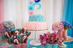 bolo de chantininho azul e rosa para chá revelação. Mesa com potinhas de cerâmica com flores e pirulitos de chocolate.