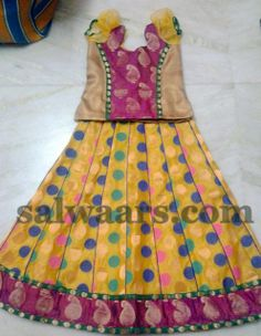Mustard yellow benaras silk kids lehenga , teamed with pink raw silk border, gold mango zari work applique on the border and multi color polka dots throughout the lehenga. Paired with gold and pink puffed sleeves designer blouse.