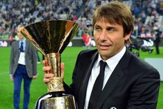 Juventus' coach Antonio Conte celebrates with the trophy during the ceremony of the Scudetto, the Italian Serie A trophy after the Italian Serie A football match between Juventus and Cagliari at the 'Juventus Stadium' in Turin on May 11, 2013