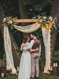 A Cozy Rustic Wedding Arch With String Lights Neutral Fabric Lush Florals And Candles On Tree Slices Around Simple Wedding Arch, Wedding Arch Rustic, Wedding Ceremony Arch, Wedding Vows, Boho Wedding, Fall Wedding, Wedding Flowers, Dream Wedding, Wedding Arches