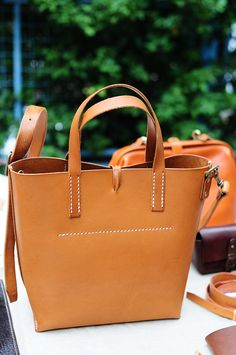 Hand stitched with good quality vegetable tanned cow leather - Stylish and special - suitable volume for daily use - it can include a pouch, wallet, coincase and cellphone. - Strap can be removed and became a tote bag - Approx. dimension : 32cm (L) (measured at the rim of the