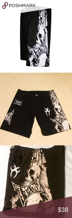 """Custom Tapout Gear Skull Shorts These custom shorts have the the Tapout skull logo on both legs. Each leg has a custom patch. 1 is a TKO Texas Kombat Organization and the other has a silver tribal patch associated with the club. Velcro and drawstring closure on the waist. 10"""" inseam (22"""" total length waist to hem) 40"""" waist. Excellent/like new condition. TAPOUT Shorts Athletic"""