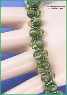"Jewelry is made with small beads. Some are glass or stone. Adult supervision is recommended. This bracelet is made with Miyuki 11/0 round silver lined olive green glass seed beads along with 4mm olive green Chinese bicone glass crystals, and is accented with 6mm round olive green cats eye glass beads and hooks with a lobster claw clasp. Measures approx. 8 3/8"" long (including clasp) by 3/8"" wide and is a design pattern from: Korean Design. Priced at only $25.00 with ""FREE SHIPPING"""