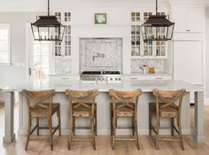 White kitchen with rustic island chairs/stools and lantern style pendants