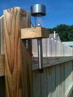 "Fence Solar Lighting = 2x4's cut to 2.5 inches long, drill 1 inch hole, attach to fence posts with ""L"" brackets, and drop the Dollar Tree solar lights in the hole. TAH-DAH!!! Cheap, easy, and beautiful lighting around the entire back yard. Yes!!!"