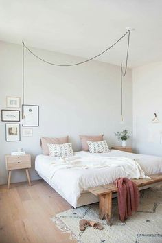 Love the exposed lighting in this bedroom. Combination of plush white comforter with dusty pink pillows and wooden bench for end of the bed. Added decorative touch with photograph / art collage, geometric knit rug and grey walls
