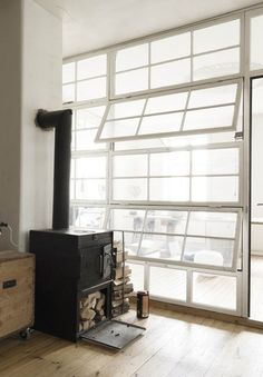 Woodstove Wood Stove Fireplace Wall of Windows Bleached Plank Floor Industrial Country