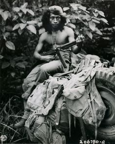 Amicedo Farola, of Dulag, Leyte, is a Philippine guerrilla scout, operating with a reconnaissance squadron of the 24th Division. The hair dress may be unusual, but Farola has more Japanese kills to his credit than he will admit to strangers. His associates confirm his scouting and fighting ability. Digos, Mindanao, March 26, 1945. US Army Signal Corps Photo.