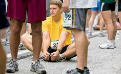 Man stretching on the ground before a race