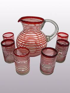 'Ruby Red Spiral' pitcher and 6 drinking glasses set by DISADI. $84.99. Handcrafted by an artisan in the town of Tonala, Mexico.. PITCHER: 84 fluid ounces ; GLASSES: 14 fluid ounces. PITCHER: Diam: 10.2'', Height: 9.4'' ; GLASSES: Diam: 3.3'', Height: 5.1''. Hand blown of recycled glass, creating unique variations on each piece.. Dishwasher safe, top rack recommended.. Swirls of ruby red embelish this set, perfect for serving cool drinks on a hot summer day.
